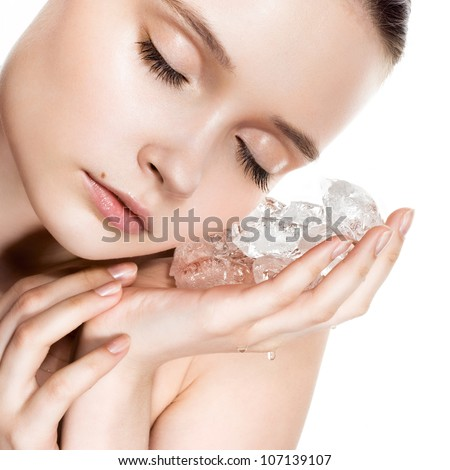 Beautiful woman with natural looking makeup holding ice cubes near face - stock photo