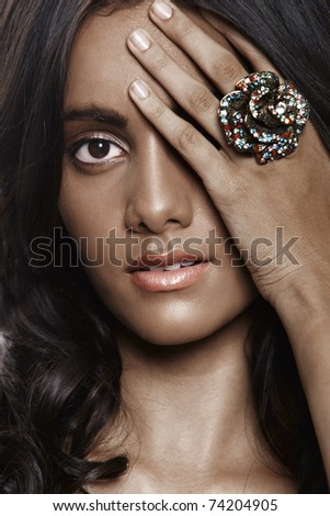 beautiful woman with natural make-up and long curly hair closes her eye with hand wearing big flower ring. - stock photo