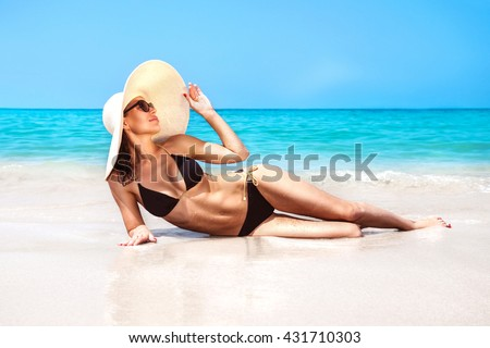 Beautiful woman with perfect body lying down on the beach, wearing stylish hat, tanning on a beach resort, enjoying summer vacation - stock photo