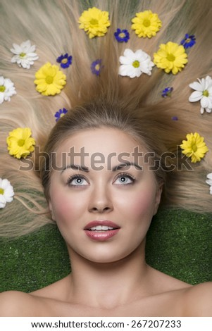 beautiful  woman with perfect skin posing in close-up beauty portrait lying on garden with some colourful flowers in her long and smooth  hair  - stock photo