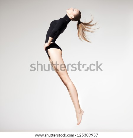 beautiful woman with perfect slim body and long legs jumping - fitness concept - stock photo