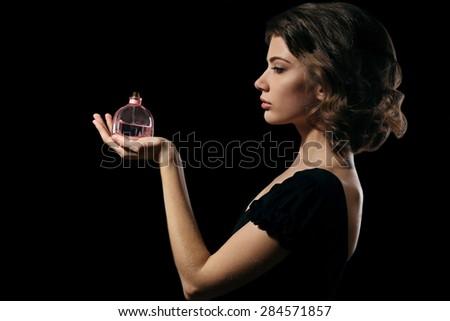 Beautiful woman with perfume bottle on black background - stock photo