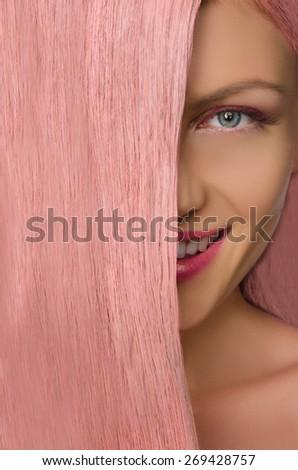Beautiful woman with pink hair looking at camera - stock photo