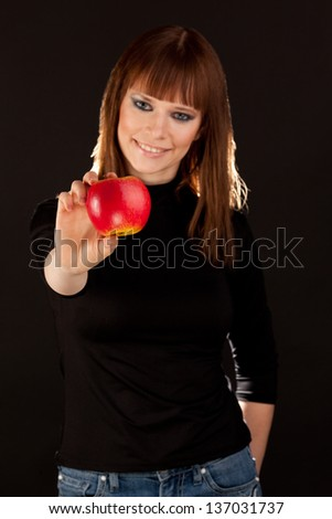 Beautiful woman with red apple smiling (focus on apple) - stock photo