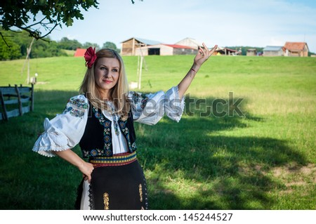 beautiful woman with red flower in her hair posing in Romanian traditional costume - stock photo