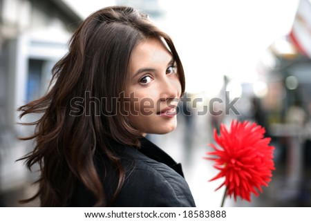 Beautiful woman with red flower walking down street, looking back. Shallow DOF. - stock photo