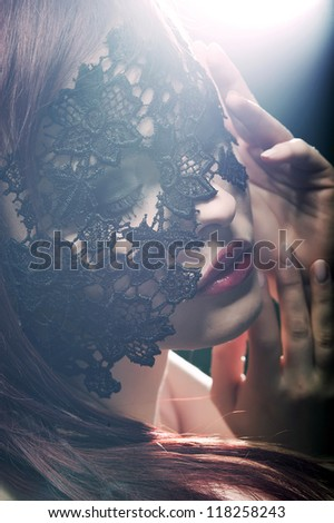 beautiful woman with red lips and lace mask over her eyes - stock photo