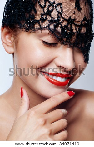beautiful woman with red lips and lace mask over her eyes. - stock photo