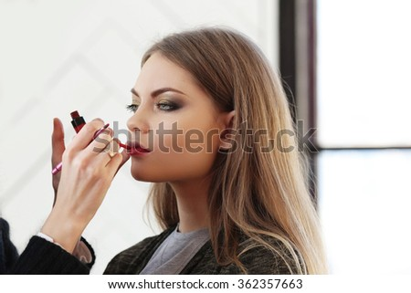 Beautiful woman with red lipstick during make-up - stock photo