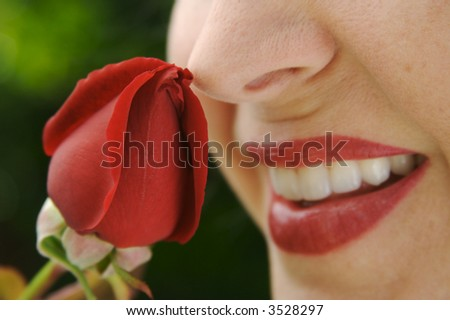 Beautiful woman with red lipstick smells a rose bud. Focus in on the rose. - stock photo