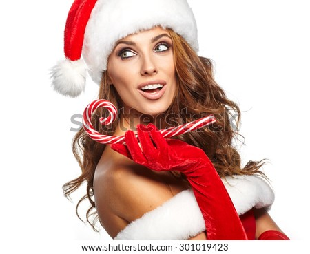 Beautiful woman with santa hat holding red -white Christmas Lollipop - stock photo