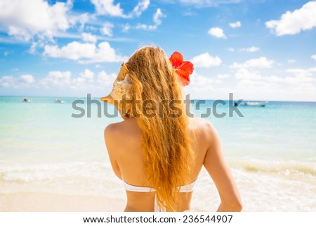 Beautiful woman with sea shell enjoying beach listening to ocean sound happy girl holding seashell, relaxing in nature, summer travel vacation spa paradise getaway destination relaxation concept - stock photo