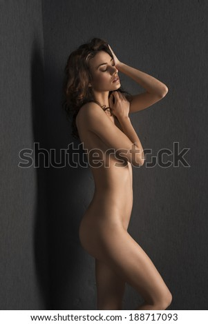 beautiful woman with sensual body , posing nude with closed eyes near a gray wall . long hair - stock photo