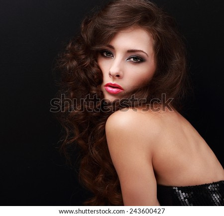 Beautiful woman with smokey eyes bright makeup and long curly hair looking on black background - stock photo