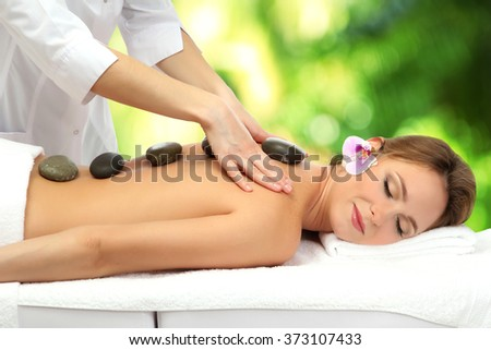 Beautiful woman with spa stones getting massage in spa salon - stock photo