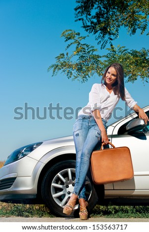 Beautiful woman with suitcase leaning on a car  - stock photo