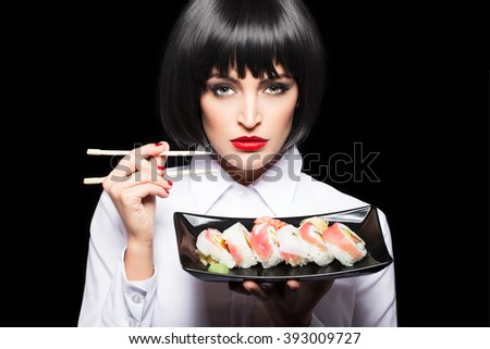 Beautiful woman with sushi rolls on plate, holding chopsticks - stock photo