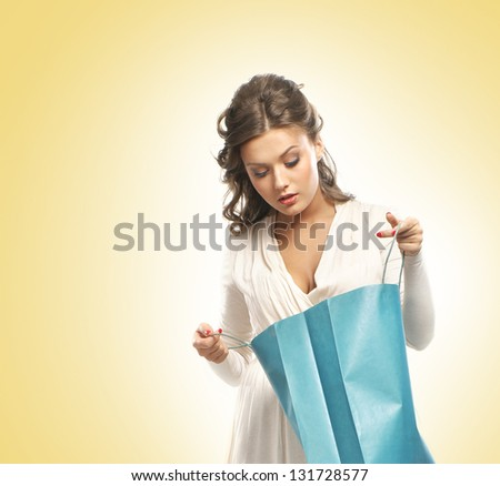 Beautiful woman with the bright shopping bags over the yellow background - stock photo
