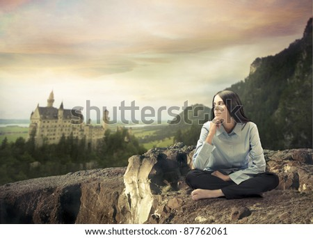 Beautiful woman with thoughtful expression and fairy tale castle in the background - stock photo