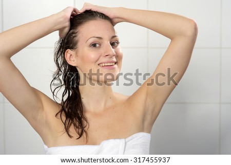 Beautiful woman with towel standing at the shower - stock photo