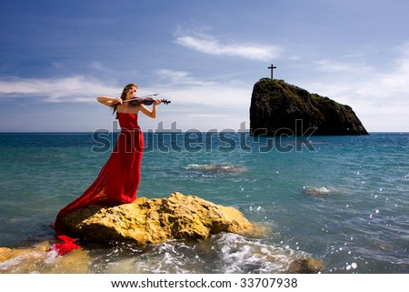 Beautiful woman with violin at the sea beach - stock photo