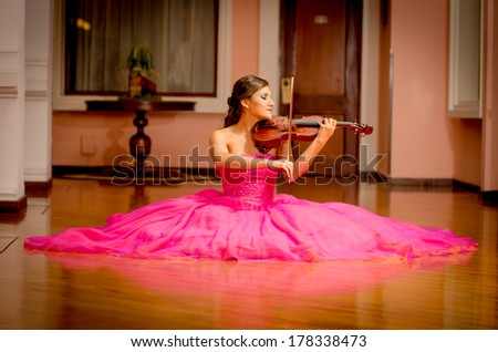 Beautiful woman with violin playing with big dress - stock photo