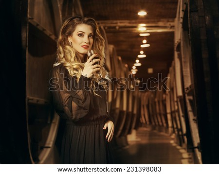 Beautiful woman with wine glass and bottle in the wine cellar on the background of the barrels. Degustation. - stock photo