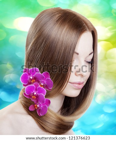 Beautiful woman with with orchids in her gorgeous hair - stock photo