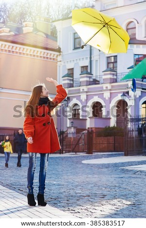 beautiful woman with yellow umbrella walks through the city - stock photo