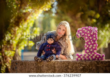 Beautiful woman with young daughter in green garden - stock photo