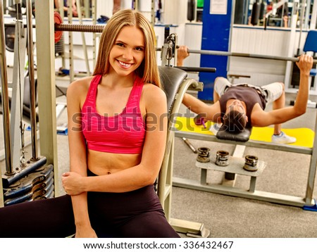 Beautiful woman working  at gym. Man lifting barbell. - stock photo