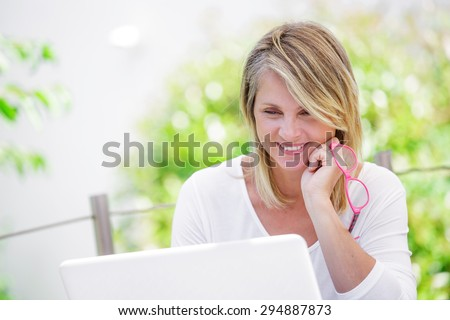beautiful woman working on a computer at home with green garden on her background - stock photo
