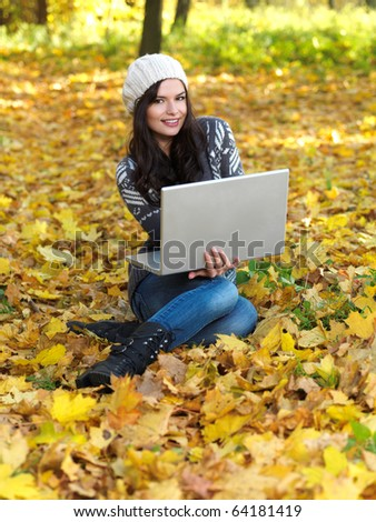 Beautiful woman working on laptop in park during autumn season - stock photo