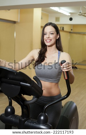 Beautiful woman working out in a health club on elliptical trainer. - stock photo