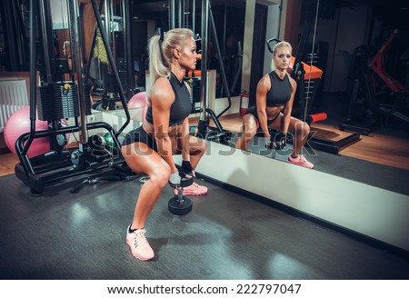 beautiful woman working out with a dumbbells in a gym - stock photo