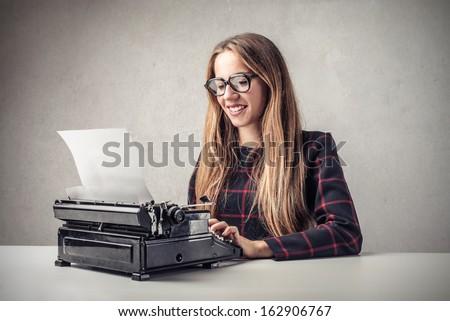 beautiful woman writing with a typewriter - stock photo