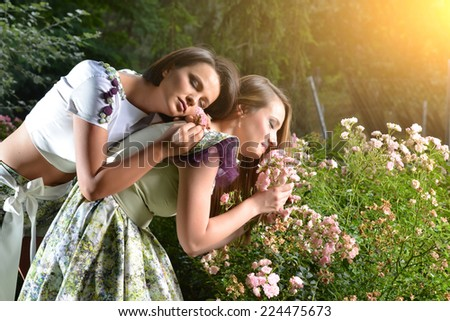 Beautiful women among blooming trees, Spring , Summer beauty. Young Blonde women posing on a rose flowers . Horizontal, Outdoor shot. Colorful photography - stock photo