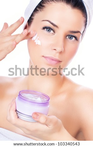 Beautiful women applying moisturizer cosmetic  cream on face - stock photo