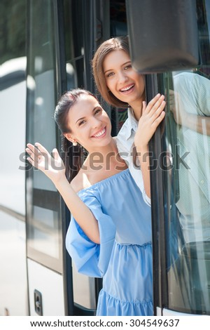 Beautiful women are beginning their trip. They are standing on doorsteps of a bus. The friend are raising their palms and saying goodbye. They are embracing and smiling - stock photo