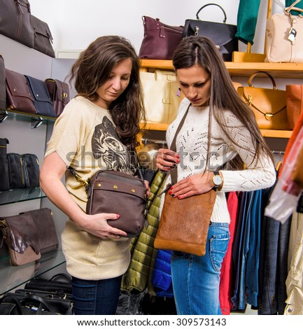 Beautiful women choosing leather bags in the store - stock photo