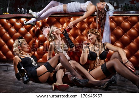 Beautiful women in evening dresses with champagne glasses nest to bar counter - stock photo