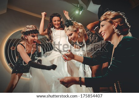 Beautiful women in evening dresses with scissors cutting bride`s dress - stock photo
