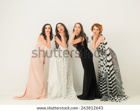 beautiful women in long dresses blowing sweet kisses in front of the camera - stock photo