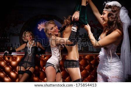 Beautiful women in retro underwear undressing their girlfriend next to bar counter - stock photo
