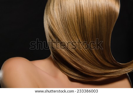 Beautiful women's light straightened out hair on black background - stock photo