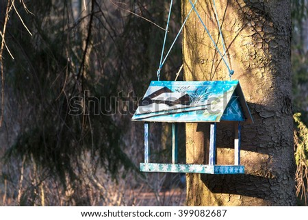 Beautiful wooden birdhouse feeder (nesting box) hanging on a tree in the park. Taking care of animals. Spring is coming. - stock photo
