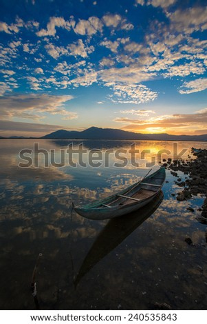 Beautiful wooden boat on lake in early morning - stock photo