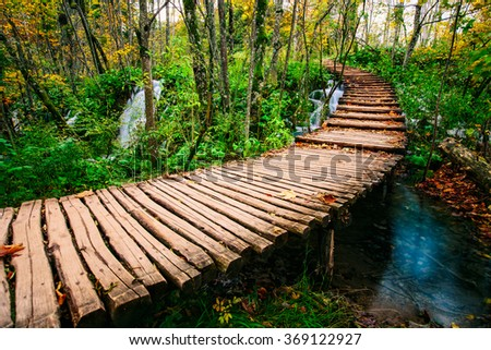 Beautiful wooden bridge pathway in the deep forest over a turquoise colored water creek in Plitvice, Croatia, UNESCO world heritage - stock photo