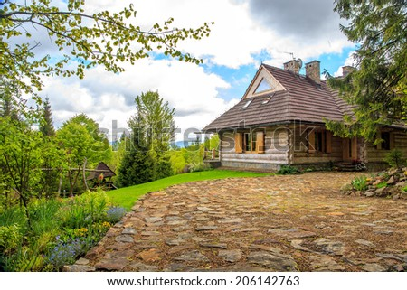 Beautiful wooden cottage somewhere in forest - stock photo