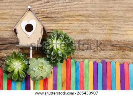 Beautiful wooden house and colorful fence (miniatures). Wooden background, copy space - stock photo